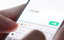 Sending I Love You Text Message With Mobile Phone. Online Dating, Texting Or Catfishing Concept. Romance Fraud, Scam Or Deceit With Smartphone. Man Writing Comment. Fake Profile. Internet Safety.