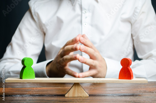 A man with hands in the lock and looks at the rival red and green figures on a scales Canvas Print