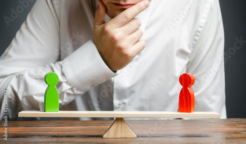 Photo Man holds hand on chin looks at the rival red and green figures on a scales