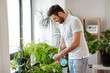 people, nature and plants care concept - man spraying houseplants by water sprayer at home