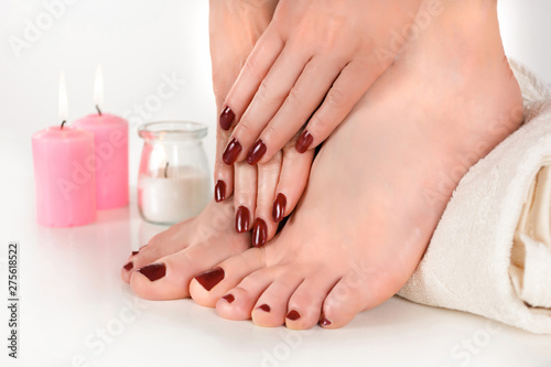 Canvas Prints Pedicure Female beautiful feet with burgundy color pedicure and hands with manicure on towel and candle in the background in beauty studio. Manicure and pedicure concept. Close up, selective focus