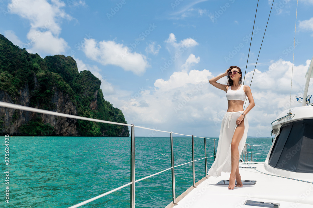 Fototapety, obrazy: Young beautiful girl with long hair standing on the bow of the yacht in white skirt and bikini. Horizontal pictures