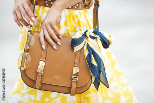 Poster Ecole de Danse Women accessories closeup picture. Purse, sunglasses and the .kerchief. Brown handbag with fashion details.