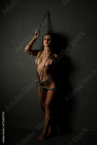 Naked woman wrapped with chain shot