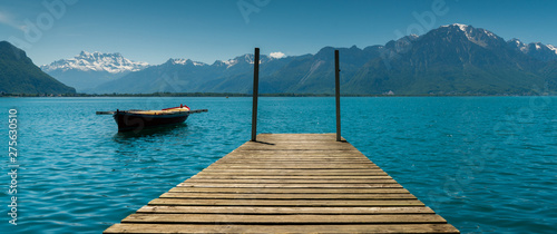 mountain and lake landscape with a vintage rescue rowboat and a wooden pier Fototapet