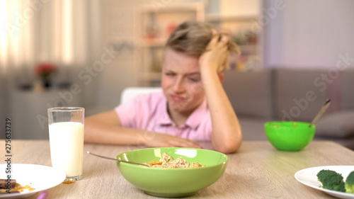 Unhappy boy looking oatmeal with disgust, unappetizing food, healthy breakfast Fototapeta