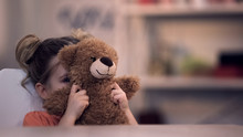 Sad Female Kid Covering Face By Teddy Bear Toy, Family Problem, Loneliness Abuse