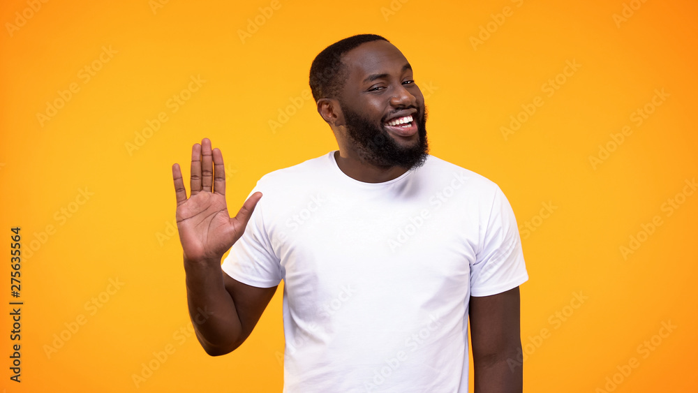 Fototapety, obrazy: Affable young black man showing palm, waving hand neighborly yellow background