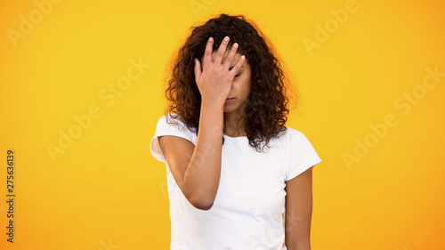 Tablou Canvas Discontent biracial lady gesturing face palm on camera against yellow background