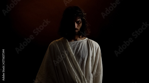 Fotografia God Jesus in crown of thorns standing in dark, punishment for mortal people sins