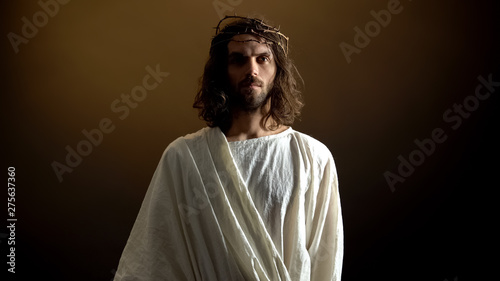 Fotografering Jesus in crown of thorns looking to camera, punishment for mortal people sins
