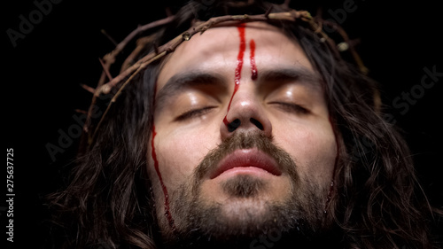 Photo Closeup of bloody Jesus head with crown of thorns, crucifying Christ, agony