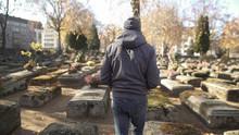 Sad Man Walking On Ancient Cemetery, Visiting Relative, Commemorating Ancestors