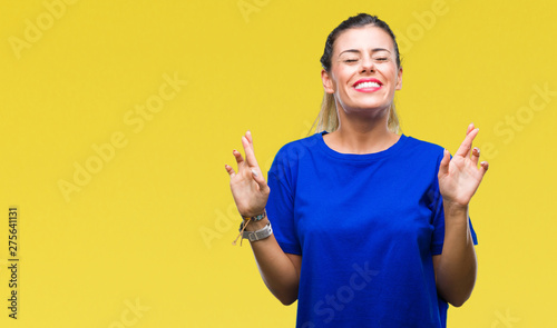 Valokuva  Young beautiful woman wearing casual blue t-shirt over isolated background smiling crossing fingers with hope and eyes closed