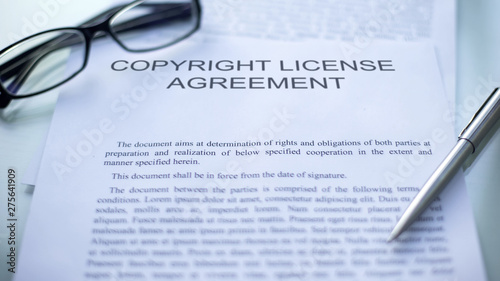 Copyright license agreement lying on table, pen and eyeglasses on document Wallpaper Mural