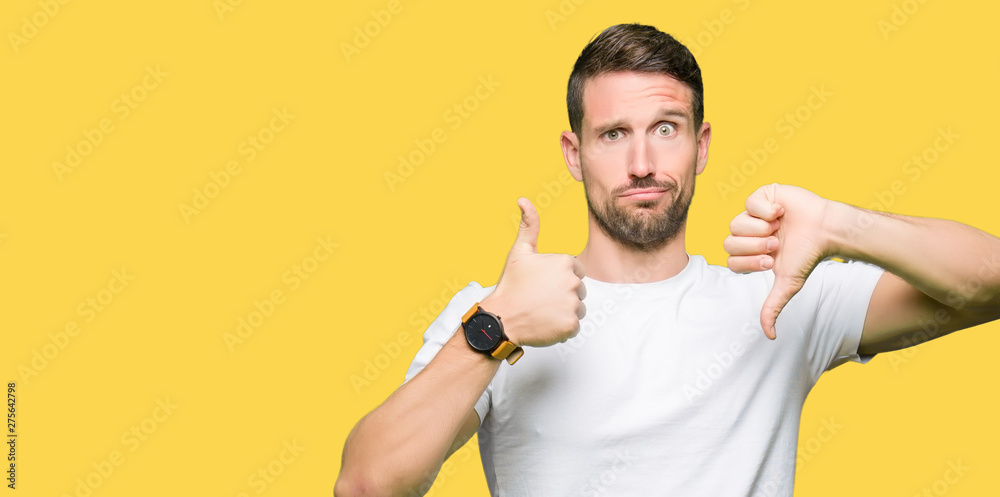 Fototapeta Handsome man wearing casual white t-shirt Doing thumbs up and down, disagreement and agreement expression. Crazy conflict