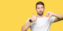 Handsome Man Wearing Casual White T-shirt Doing Thumbs Up And Down, Disagreement And Agreement Expression. Crazy Conflict