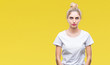 Leinwandbild Motiv Young beautiful blonde woman wearing white t-shirt over isolated background with serious expression on face. Simple and natural looking at the camera.