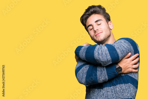 Pinturas sobre lienzo  Young handsome man over isolated background Hugging oneself happy and positive, smiling confident