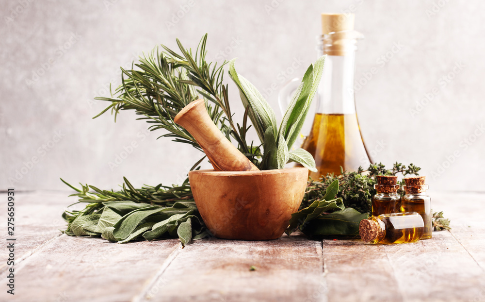 Fototapeta Fresh herbs from the garden and the different types of oils for massage and aromatherapy on table
