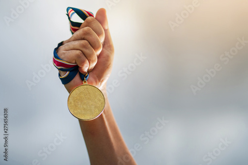 Photo Hand holding gold medal on sky background