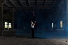 A Young Girl And Boy Perform Acrobatic Moves, Are In The Premises Of The Old Factory, The Composition, Blue Smoke Around Them, Acro