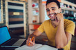 Portrait of happy hipster guy looking at camera and smiling while sitting at desktop with laptop computer for e learning and textbook for knowledge education, cheerful male student feeling good