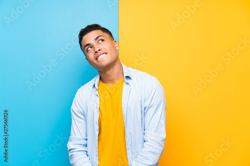 Photographie  Young man over isolated colorful background laughing and looking up
