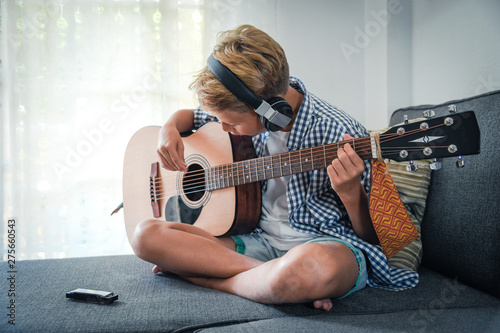 Beautiful young boy playing acoustic guitar with headphones. Music student exercises alone at home. Trendy caucasian child plays instruments sitting on the sofa. Young boy doing musical homework - 275660543