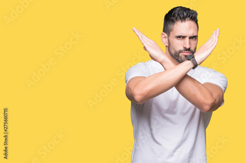 Cuadros en Lienzo  Handsome man wearing white t-shirt over yellow isolated background Rejection exp