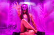 canvas print picture - Beautiful woman in a cat mask and high heels sitting in a mylar tent under ultraviolet lighting.