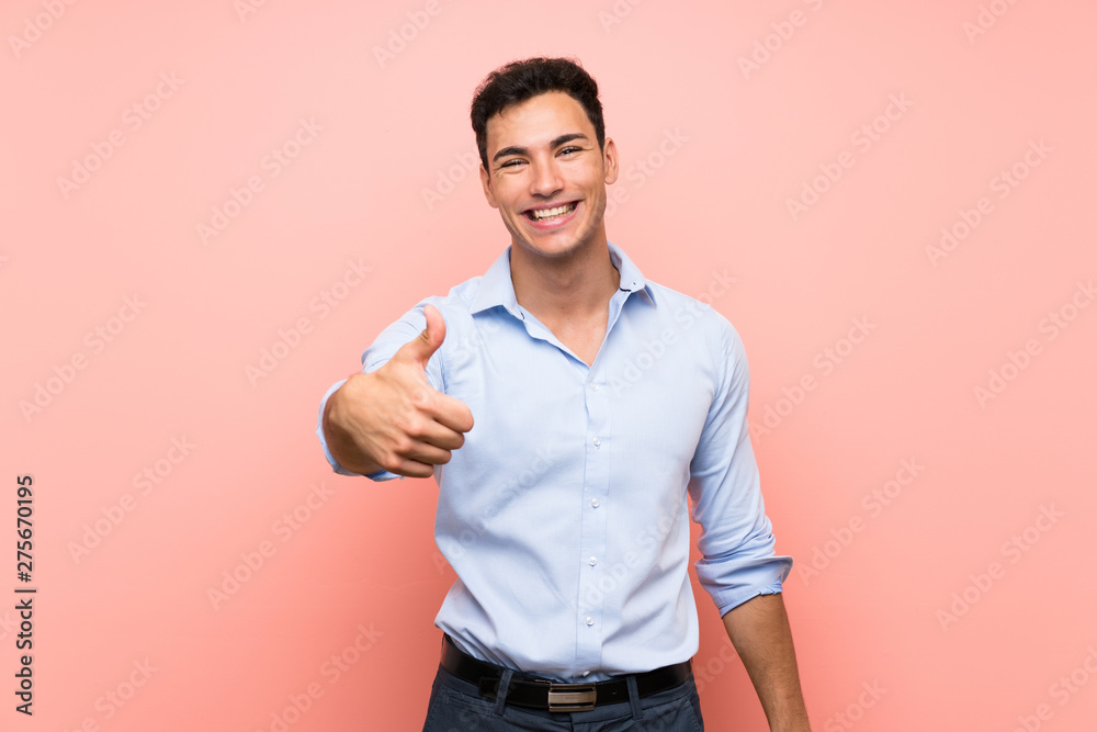 Fototapeta Handsome man over pink background with thumbs up because something good has happened