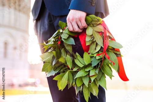 Fotografie, Obraz  Giovane laureato con corona d'alloro verde e nastro rosso tenuto in mano