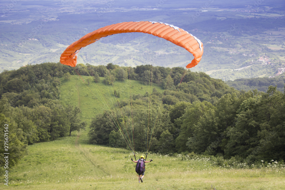 Fototapety, obrazy: Paraglider taking off from the edge of the mountain