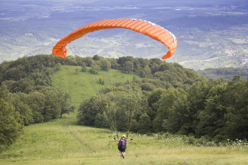 Paraglider taking off from the edge of the mountain
