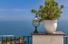 Vase Plant And Lamp On Wall With Sea Background. Amalfi Coast Situated In Province Of Salerno, In The Region Of Campania, Italy.