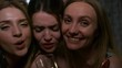 Close-up racking focus three shot of young beautiful 20 something partying girls posing for the camera in dark room, pulling funny faces, blowing kisses and toasting with glass of champagne
