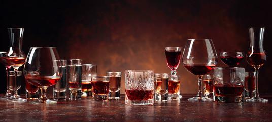 Set jakih alkoholnih pića u čašama na smeđoj pozadini.