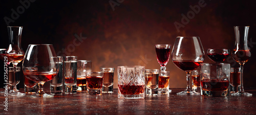 Set of strong alcoholic beverages in glasses on a brown background.