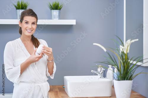 Obraz na plátně  Beautiful brunette woman applying face cream in the bathroom