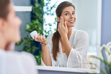 Beautiful Brunette Woman Applying Face Cream In The Bathroom