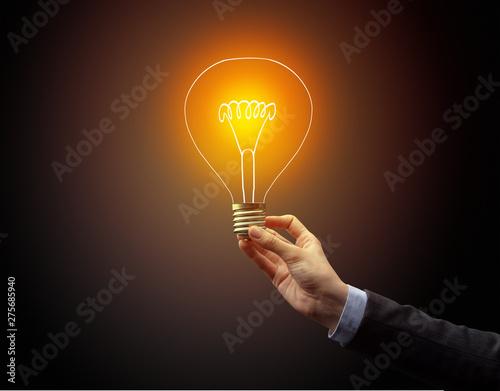 Fototapety, obrazy: Hand holding light bulb on dark background, new idea concept
