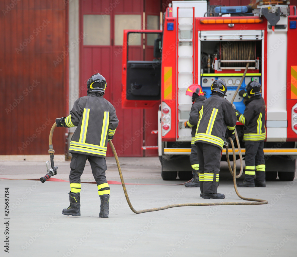 Fototapety, obrazy: three firefighters in action and the fire engine with hose