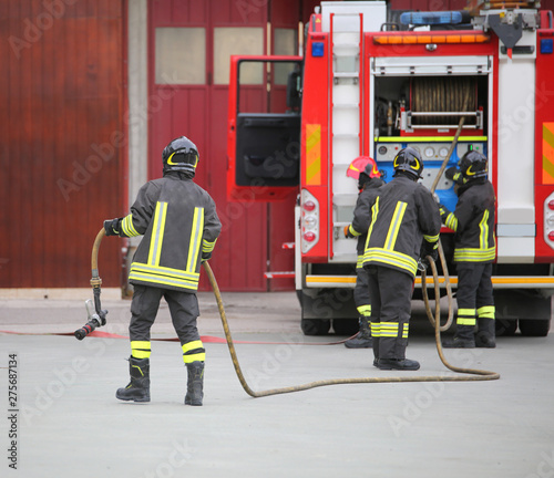 Fotografía three firefighters in action and the fire engine with hose
