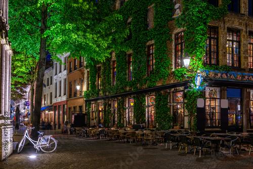 In de dag Antwerpen Old cozy narrow street with tables of restaurant in historic city center of Antwerpen (Antwerp), Belgium. Night cityscape of Antwerp. Architecture and landmark of Antwerpen