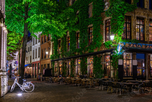 Poster Antwerp Old cozy narrow street with tables of restaurant in historic city center of Antwerpen (Antwerp), Belgium. Night cityscape of Antwerp. Architecture and landmark of Antwerpen