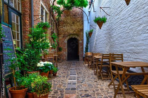 Staande foto Antwerpen Old cozy narrow street with tables of restaurant in historic city center of Antwerpen (Antwerp), Belgium. Night cityscape of Antwerp. Architecture and landmark of Antwerpen