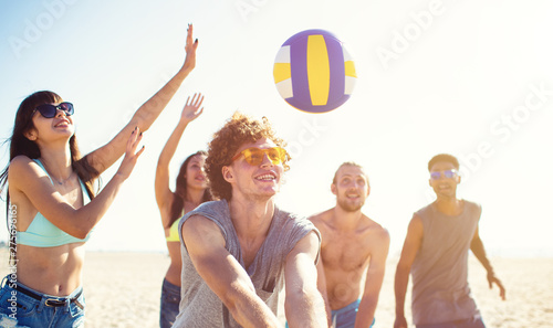 Fotografie, Obraz  Group of friends playing at beach volley at the beach