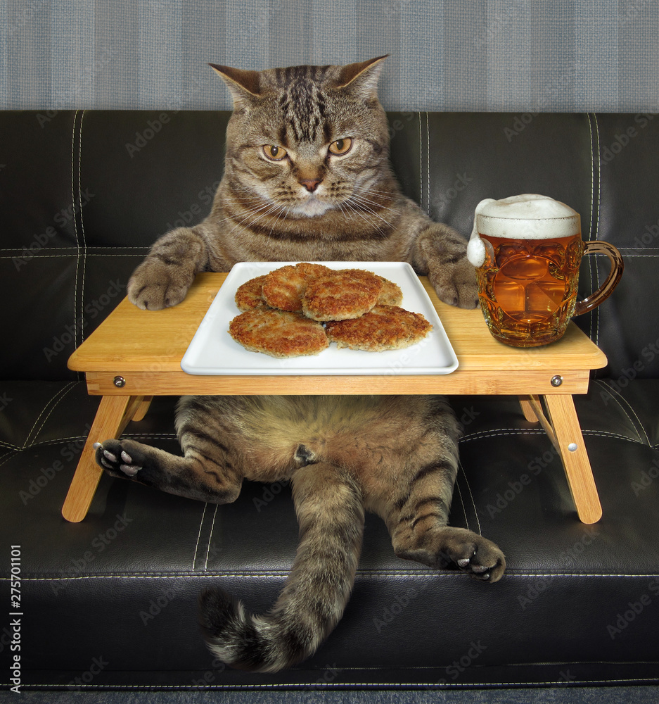 Fototapety, obrazy: The cat is eating fried cutlets and drinking beer from the folding wooden bed tray on the sofa.