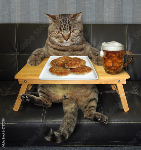 The cat is eating fried cutlets and drinking beer from the folding wooden bed tray on the sofa.